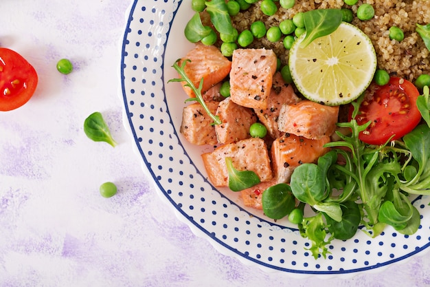 Healthy dinner. slices of grilled salmon, quinoa, green peas, tomato, lime and lettuce leaves. flat lay.