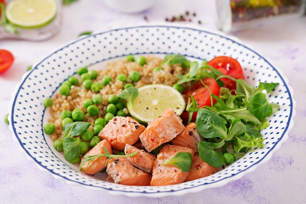 Healthy dinner. slices of grilled salmon, quinoa, green peas, tomato, lime and lettuce