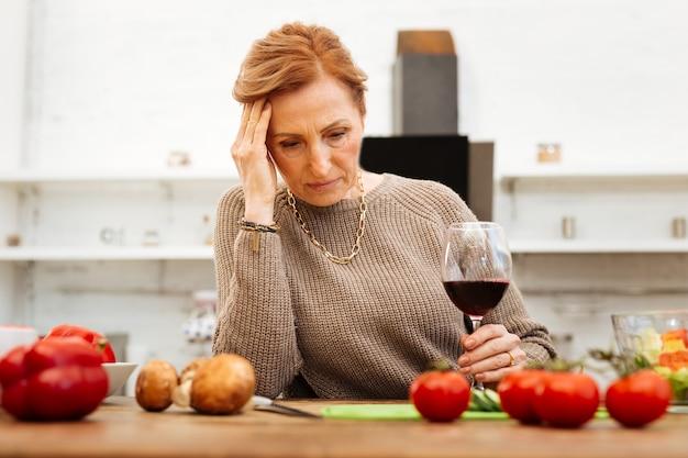 健康的な夕食。暖かいベージュのセーターを着て、ワインを一人で飲む髪を結んだ、動揺したハンサムな女性