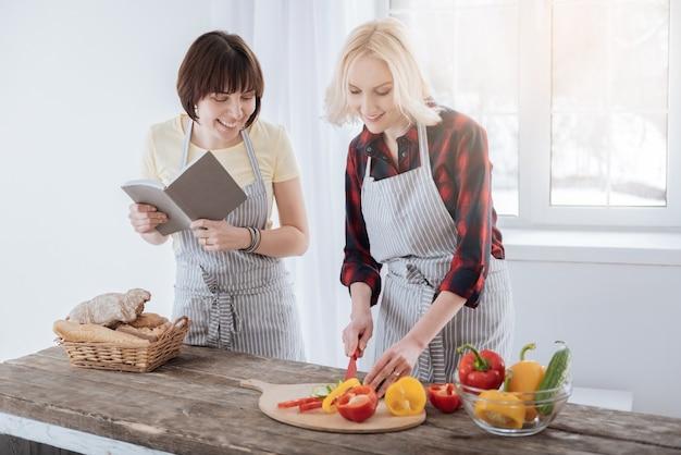 건강한 요리. 샐러드를 준비하는 동안 부엌에 서서 야채를 자르는 행복 좋은 긍정적 인 여자