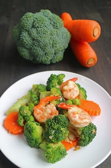 Healthy dish of prawn stir fried with broccoli and carrot served on white plate