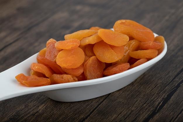 Здоровые сушеные фрукты абрикоса в белой ложке на деревянных фоне.
