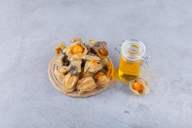 돌 테이블에 놓인 꿀과 건강 말린 cumquat 과일.