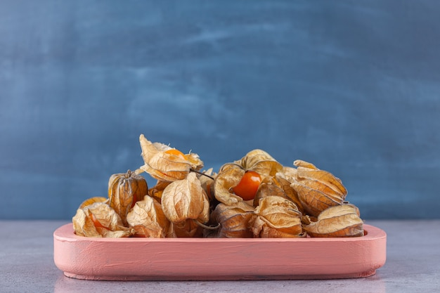 Healthy dried cumquats placed on a pink board .