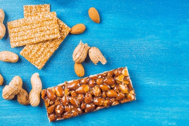 Healthy dried fruits bar with almonds and peanuts on blue background