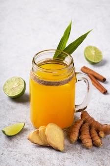 ウコンと生姜の根からの健康的な飲み物と白い背景の上のガラスのライム。
