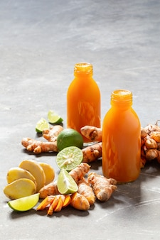 Здоровый напиток из куркумы и имбиря корни и лайм в маленьких бутылках на серую бетонную стену.