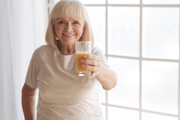 健康的な飲み物。幸せな白髪の老婆があなたを見て、窓に立っている間ジュースのグラスを提供します