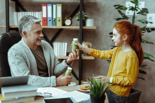 Здоровый напиток. милая милая девушка смотрит на своего отца, принимая бутылку смузи