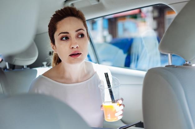 健康的な飲み物。ジュースとカップを保持し、仕事のためにタクシーに乗っている間それを飲む前向きな喜びの若い実業家