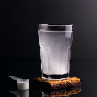 운동선수를 위한 건강 음료. 검은 배경에 유리에 흰색 음료.