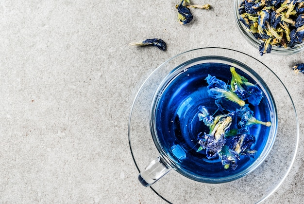 Healthy drinks, organic blue butterfly pea flower tea with limes and lemons, grey concrete background copy space above