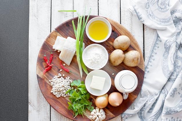 Концепция здорового питания и диеты - натуральная пища на столе. ингредиенты рыба фасоль петрушка луковый крем картофель для фрикаделек