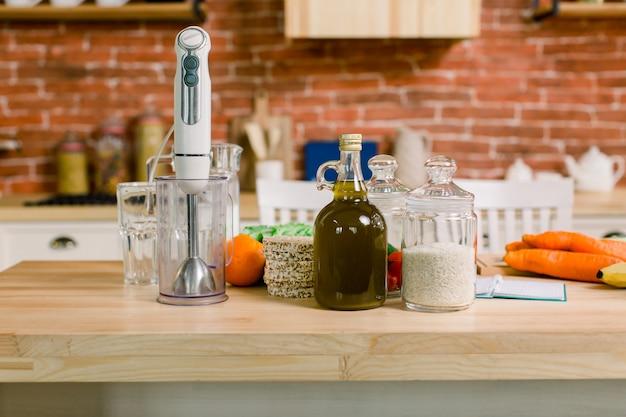 健康的な食事とダイエットのコンセプト-テーブルの上の自然食品。野菜、果物、米、オリーブオイル、グラス、ブレンダー、木製のテーブルでモダンなキッチン