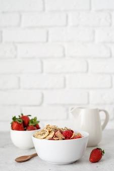 Здоровое питание и диета. здоровый завтрак, хлопья, свежие ягоды и молоко в миске на фоне белой кирпичной стены, копией пространства
