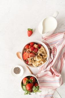 健康的な食事とダイエット。健康的な朝食、シリアル、新鮮なベリー、コピースペースのあるボウルにミルク、上面図フラットレイ