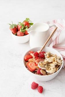 Здоровое питание и диета. здоровый завтрак, хлопья, свежие ягоды и молоко в миске с копией пространства