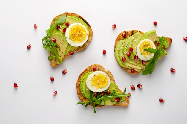 Healthy eating. avocado toasts with egg, arugula and pomegranate seeds. top view, flat lay