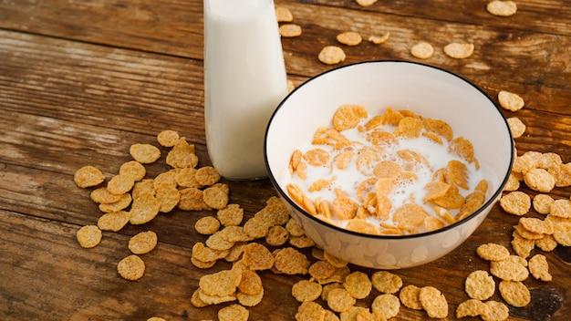 健康的な食事の背景。コーンフレークとボウルに新鮮なミルク。木製の背景。ガラス瓶に入ったミルク