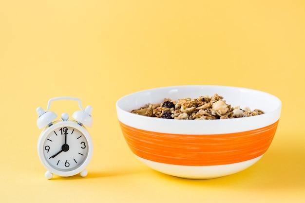 Здоровое питание. запеченный овес, орехи и мюсли в миске и будильник на желтом фоне