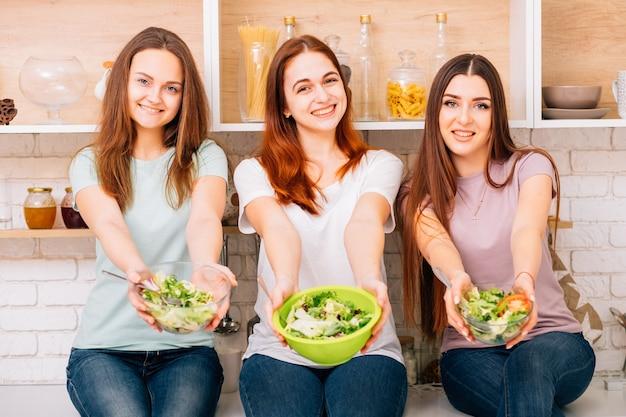건강한 식생활. 균형 잡힌 식단과 여성 피트니스. 그릇에 야채 샐러드를 들고 여자입니다.