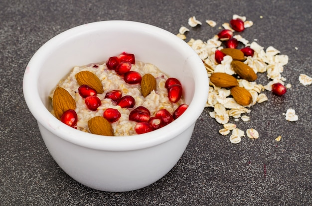 Healthy eating, breakfast. oatmeal with pomegranate and nuts, black coffee.