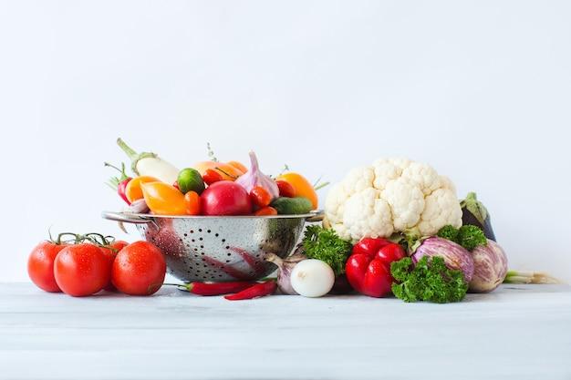 健康的な食事。木製のテーブルの上の金属ザルで新鮮な野菜をきれいにします。