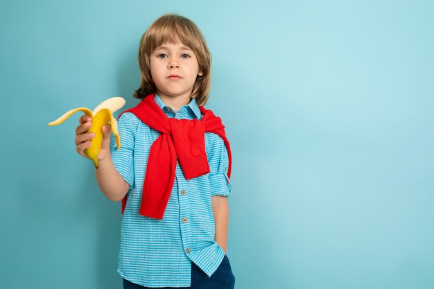 Healthy eating concept. a boy in a short-sleeved shirt holds a bitten banana on a light blue background