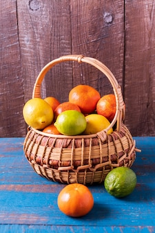 Healthy eating concept. citrus fruits in a basket over wooden background