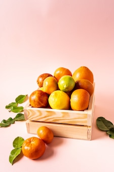 Healthy eating concept. citrus fruits in a wooden crate against a pink background