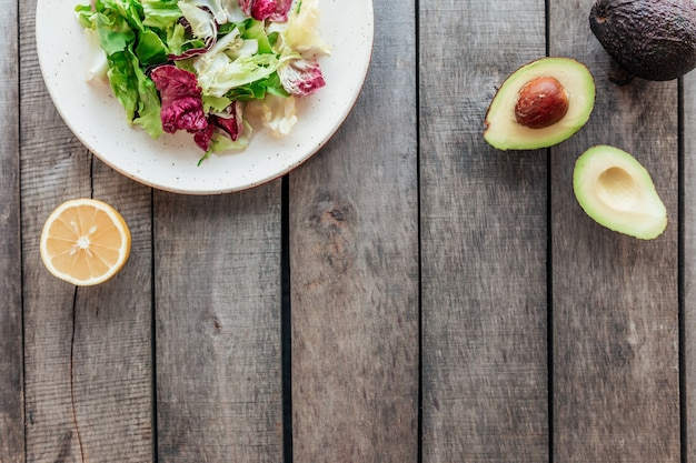 Заложить квартиру концепции здорового питания. средиземноморская диета, тарелка со свежими листьями салата из зеленого салата, фиолетовыми листьями радиккио, половинками авокадо с ядром, целым авокадо, лимоном на деревянном столе