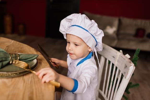 건강한 먹는 개념. 행복 한 어린 소년 화창한 여름 날에 부엌에서 요리입니다. 피크닉에 유아 베이커는 하얀 앞치마와 모자에 빵과 베이글을 먹는다
