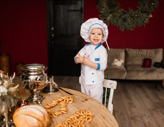 Healthy eating concept. happy little boy is cooking in kitchen on a sunny summer day. toddler baker on a picnic eats bread and bagels in a white apron and hat
