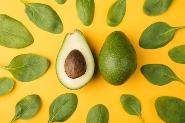 健康的な食事の概念。黄色の背景に分離された赤ちゃんほうれん草の葉に囲まれたカットアボカドの頭上のクローズアップ写真の上の上