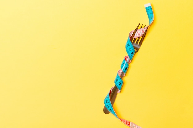 Healthy eating concept wrapped fork in measuring tape