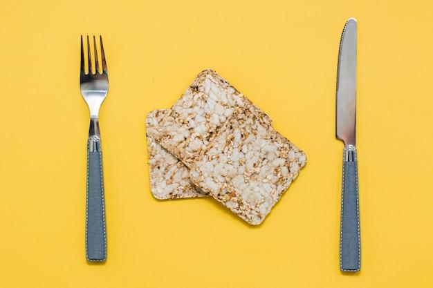 健康的な食事。オート麦、小麦、亜麻、ゴマを積み重ねたクリスプブレッドと黄色の背景のカトラリー。スーパーフード。上面図