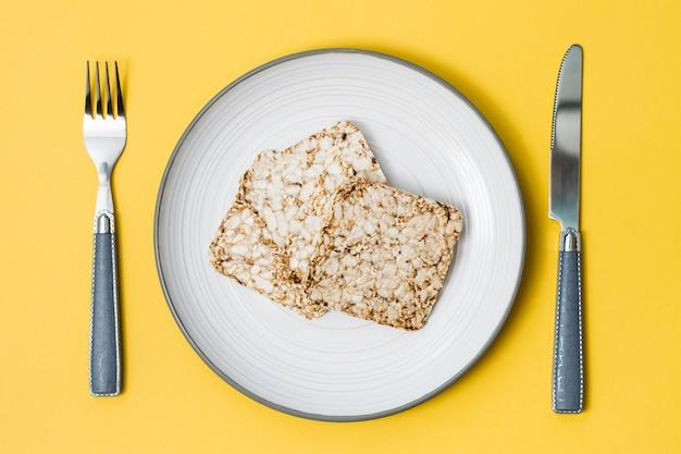 健康的な食事。オート麦、小麦、亜麻、ゴマを皿に、カトラリーを黄色の背景にしたクリスプブレッド。上面図