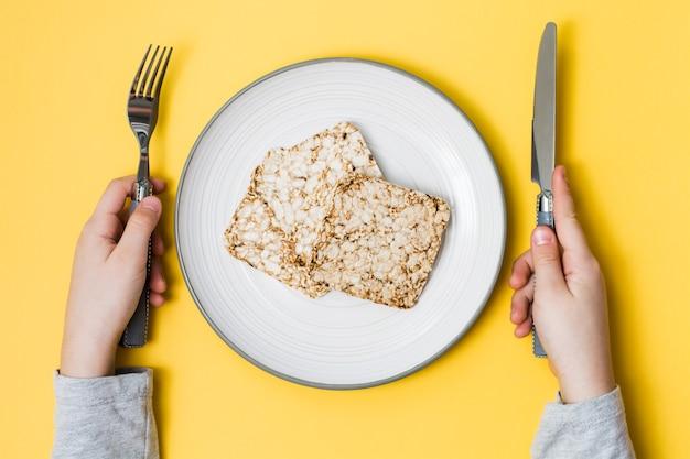 健康的な食事。オート麦、小麦、亜麻、ゴマを皿にのせて作ったクリスプブレッドと手は、黄色の背景にカトラリーを持っています。上面図