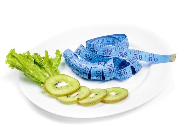 健康的な食事、ダイエットと減量、デトックス。巻尺と新鮮なキウイ