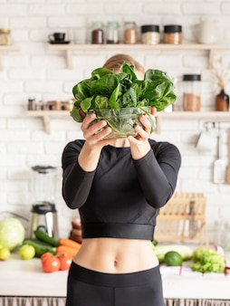 Healthy eating, diet and cooking concept. young blond smiling woman holding a bowl of fresh spinach in the kitchen