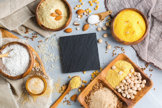 건강한 식생활, 다이어트, 균형 잡힌 음식 개념. 테이블에 글루텐 프리 밀가루, 아몬드, 옥수수, 쌀의 구색. 평면도 평면 누워 배경