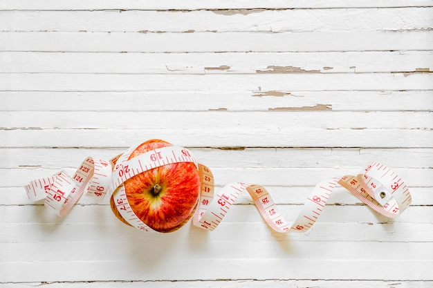 Healthy eating and dieting concept. apple and measuring tape on rusty white wood background. top view with copy space.