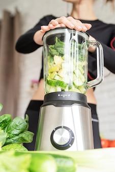 건강한 식생활, 다이어트 개념. 집 부엌에서 녹색 스무디를 만드는 젊은 금발 웃는 여자