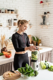 Healthy eating, dieting concept. young blond smiling woman making green smoothie at home kitchen