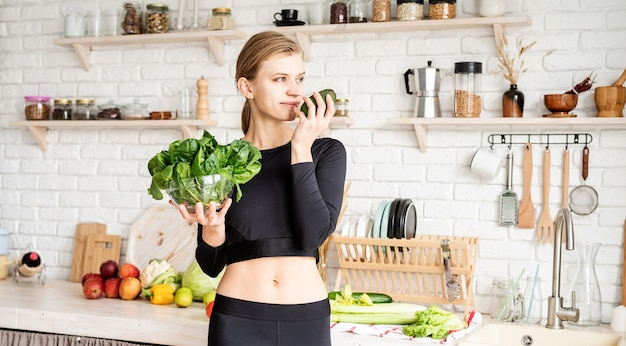 Healthy eating, dieting concept. young blond woman in sport clothes holding a bowl of fresh spinach in the kitchen