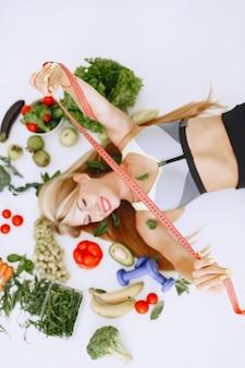 Mangiare sano. concetto di dieta e persone. bionda sdraiata sul pavimento.