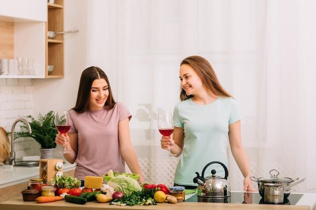 健康的な食事。一緒にダイエット。新鮮な野菜の品揃えとキッチンで2人の若い女性。グラスに赤ワイン。