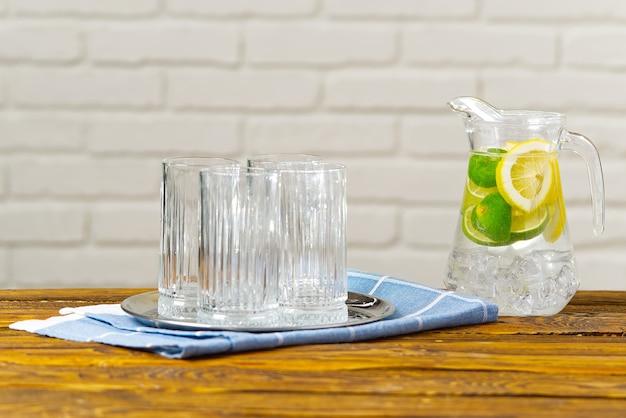 ガラスの水差しにフルーツを注入した水で女性の健康的な食事、飲み物、ダイエット、デトックスの概念のクローズアップ