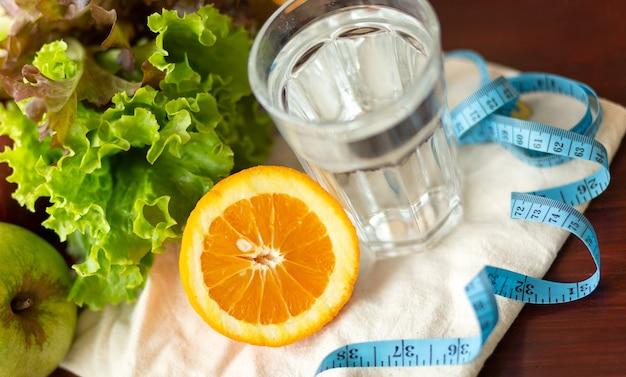 Здоровое питание, напитки, измерительная синяя лента, диета, детоксикация и люди концепции - крупным планом фруктовая вода в стакане