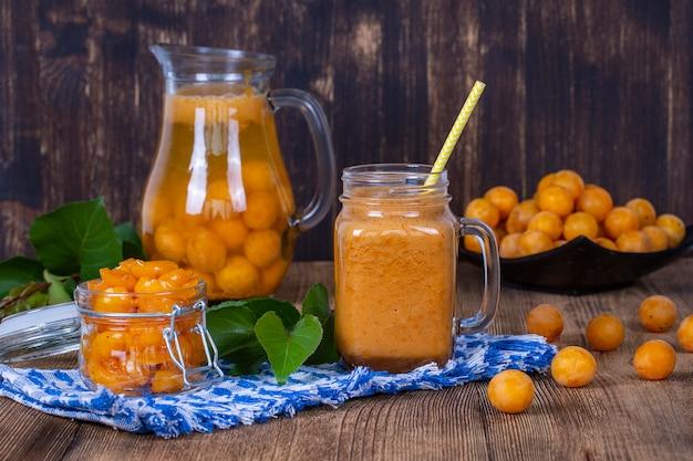健康的な食事、食べ物、ダイエット、ベジタリアンのコンセプト-木製のテーブルの上で、黄色いプラム、レモネード、ジャム、熟した黄色いプラムからジューススムージーシェイクのマグカップグラス。バイオヘルシーな食べ物と飲み物。有機ダイエット